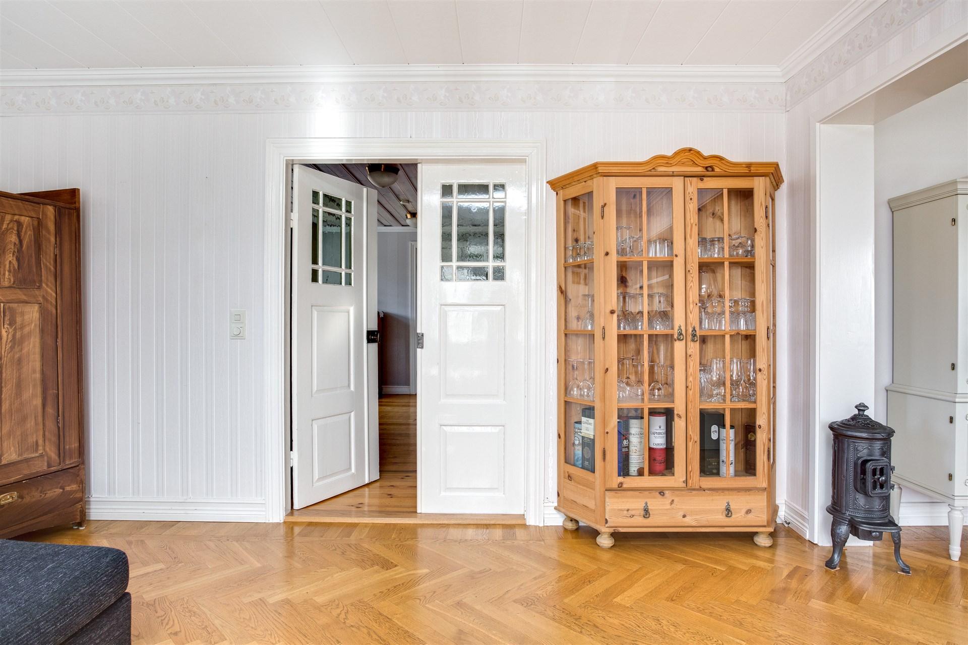 Fina dubbeldörrar som leder ut i hallen från vardagsrummet.