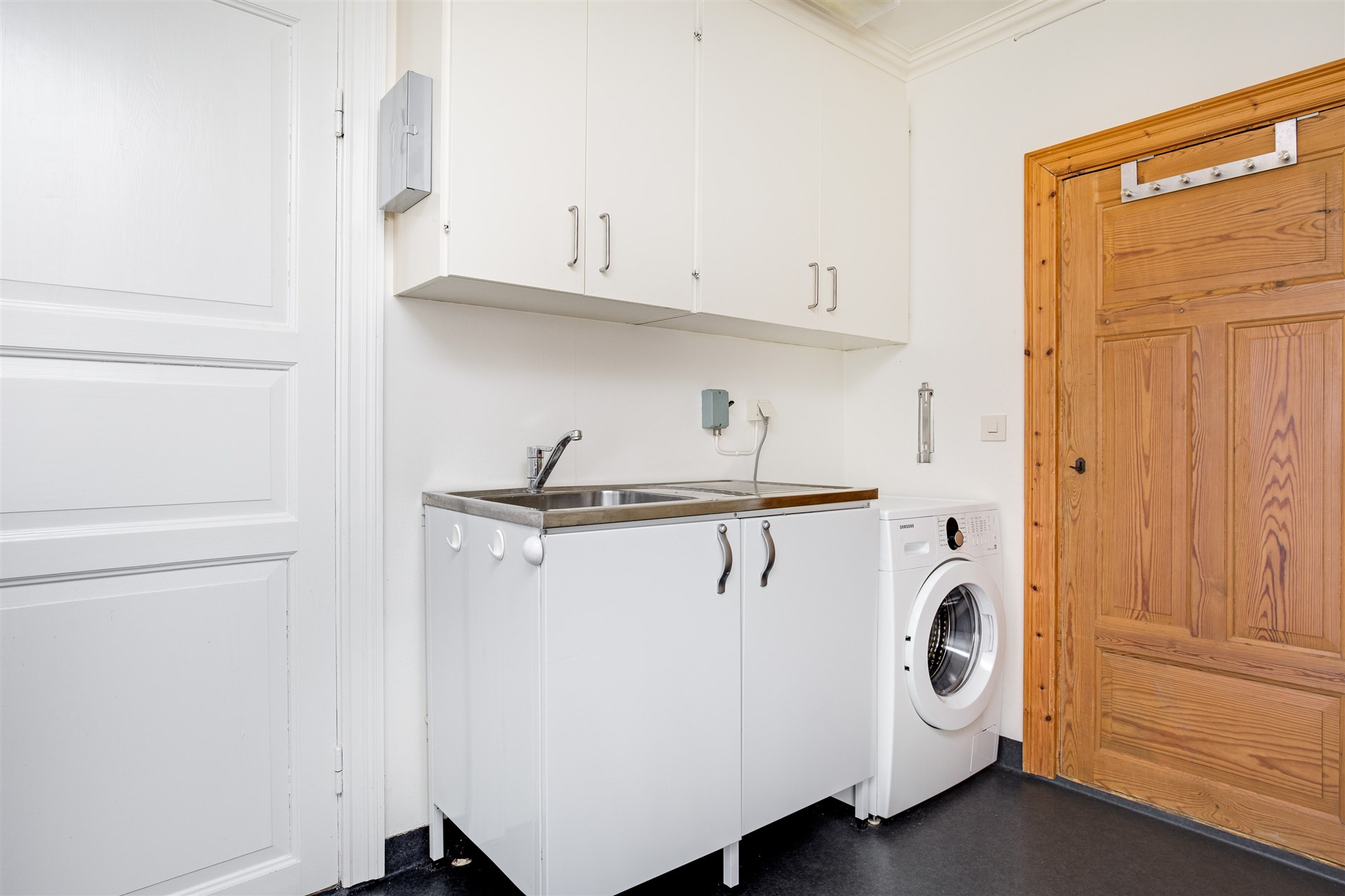 Tvättho och tvättmaskin med förråd innanför.