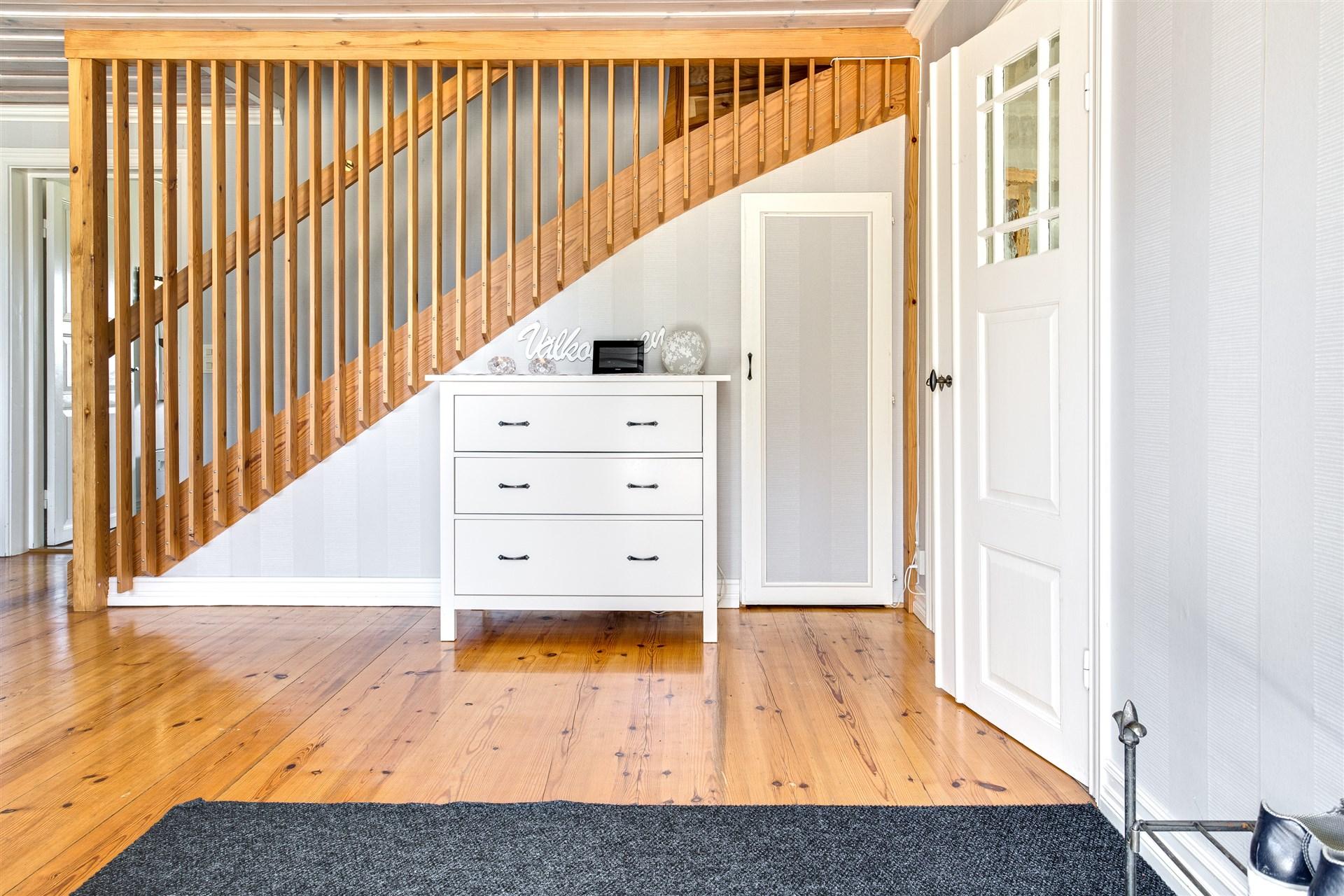Rymlig hall med trapp till övervåningen och praktisk förvaring under trappen.
