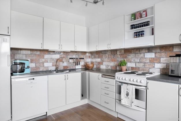 Kök med diskmaskin, ugn/spis, kyl och frys. Vackert stänkskydd i sten med rustik känsla.