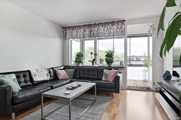 Välkommen till Trädlyckevägen 106! Vackert, ljust vardagsrum med skönt ljusinsläpp från fönstren och balkongdörren.