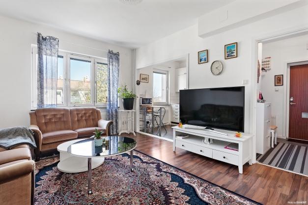 Ljust vardagsrum med öppen planlösning mot köket