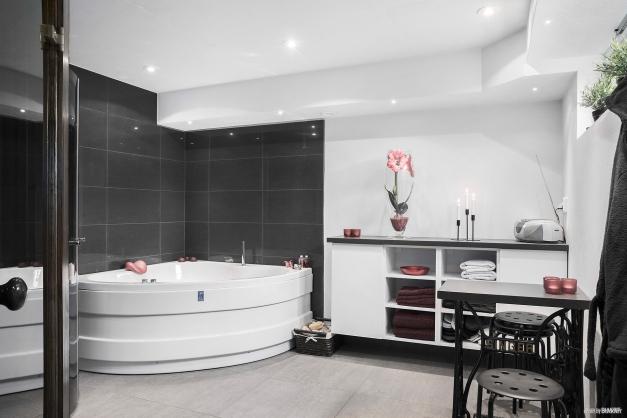 Stor relaxavdelning med både bubbelbadkar, bastu och dusch.