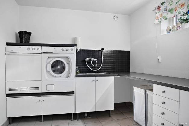 Tvättavdelning med tvättmaskin och torktumlare i bekväm arbetshöjd.