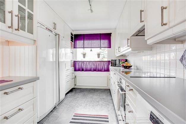 Ljust helrenoverat kök med vita luckor och grå arbetsbänk.