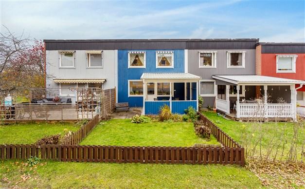 Baksidan med altan under tak och liten trädgård med staket runt om.