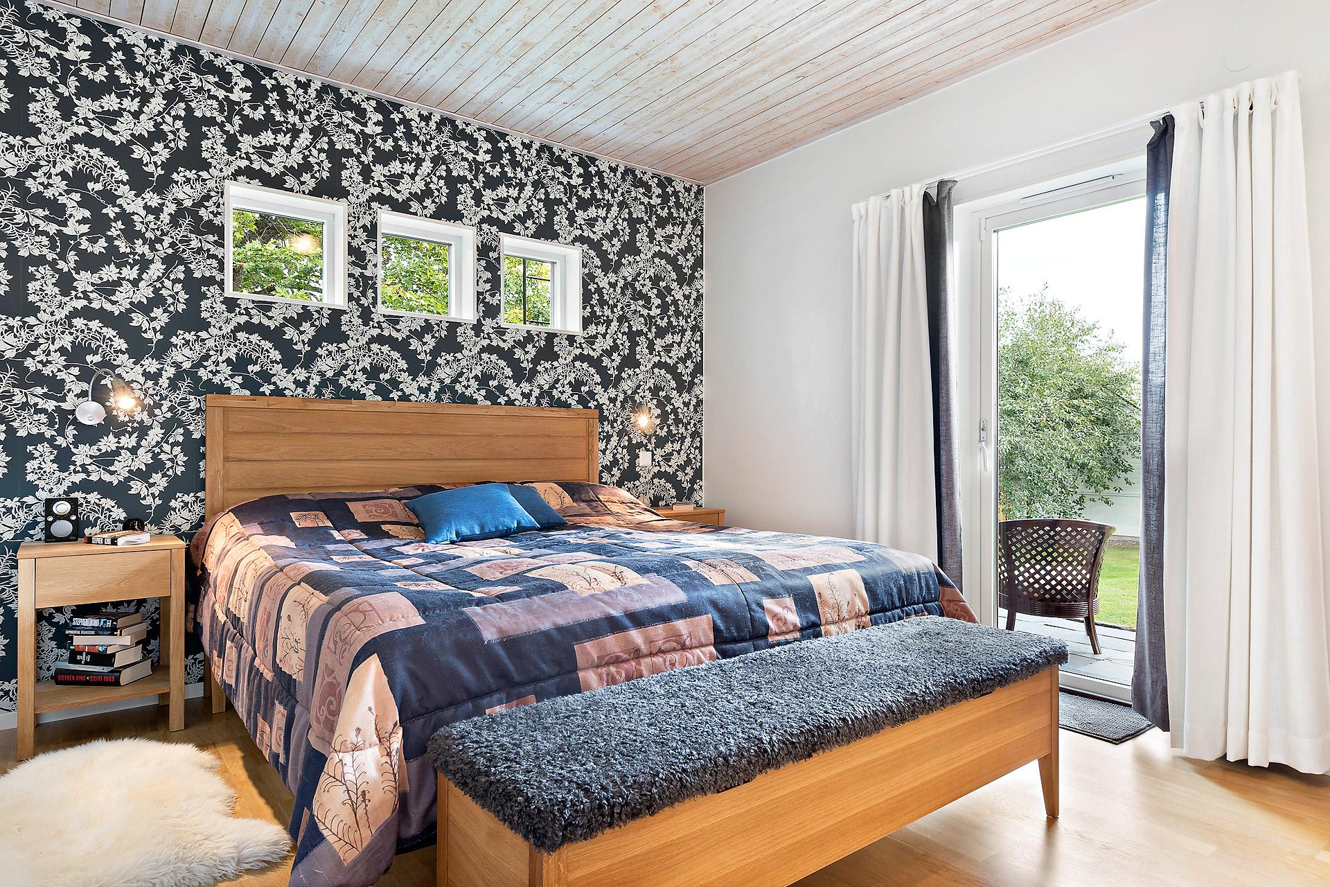 Master bedroom med utgång till stenlagd uteplats med morgonsol.