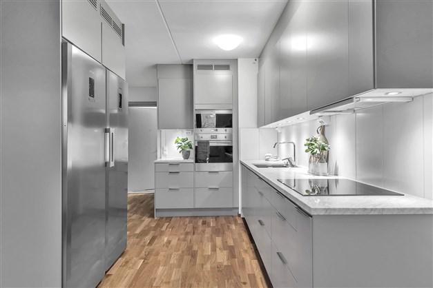 Lägenheten är tillvalsutrustad utan extra kostnad med gråa köksluckor med svagt rundade kanter. Bänkskiva med Carrara marmor och infälld diskho. Kyl och frys samt  inbyggnadsmicro och inbyggnadsugn i rostfritt.