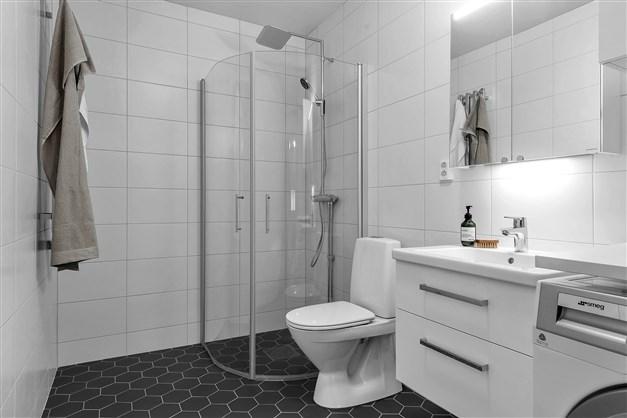 Badrummet är inrett med handfatskommod med utdragbara lådor samt spegelskåp med ledbelysning.  Duschpaket med takdusch och handduksvärmare. Grått klinkergolv, hexagon, med komfortvärme.