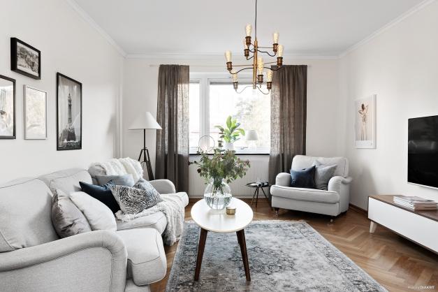Ljust vardagsrum med fiskbensparkett och stort fönster