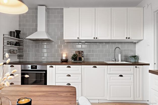 Komplett kök med klassiska materialval och integrerad diskmaskin.
