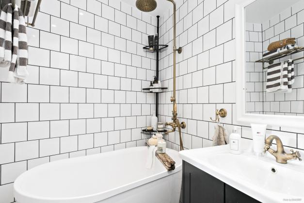 Helkaklat och stilrent badrum med genomgående fina detaljer.