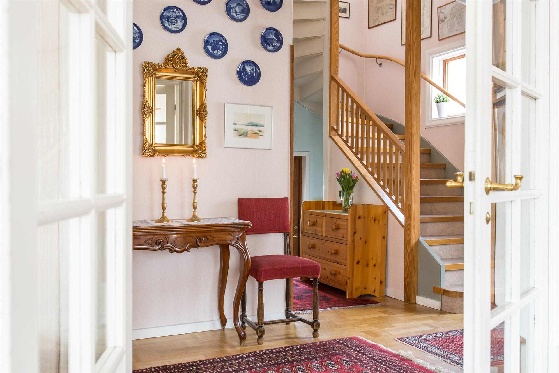 Rymlig hall med trappa till övervåningen