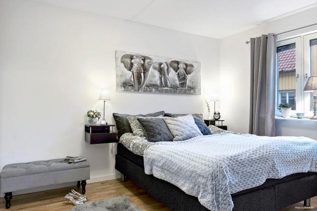 Stort sovrum med ekparkettgolv och vitmålade väggar.