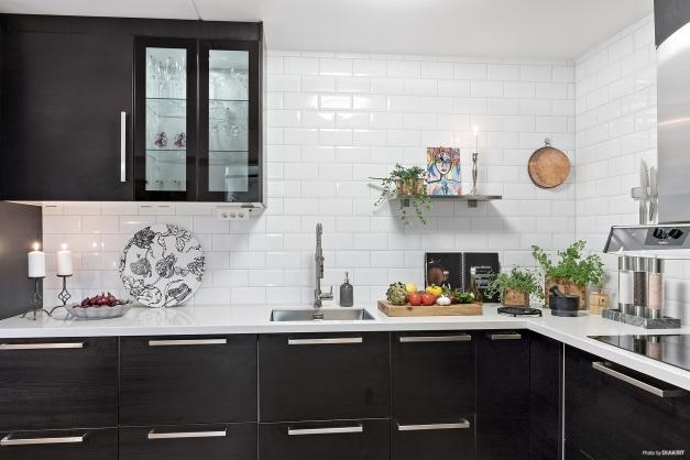 Klassiskt, vitt kakel i kombination med svart köksinredning