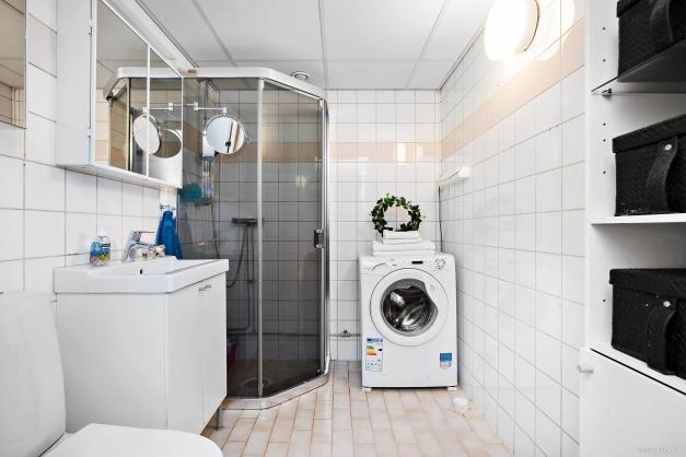 Helkaklat duschrum med wc, duschkabin och tvättmaskin. Ljusa fräscha färger. äldre ytskikt, nyare wc stol, kommod.
