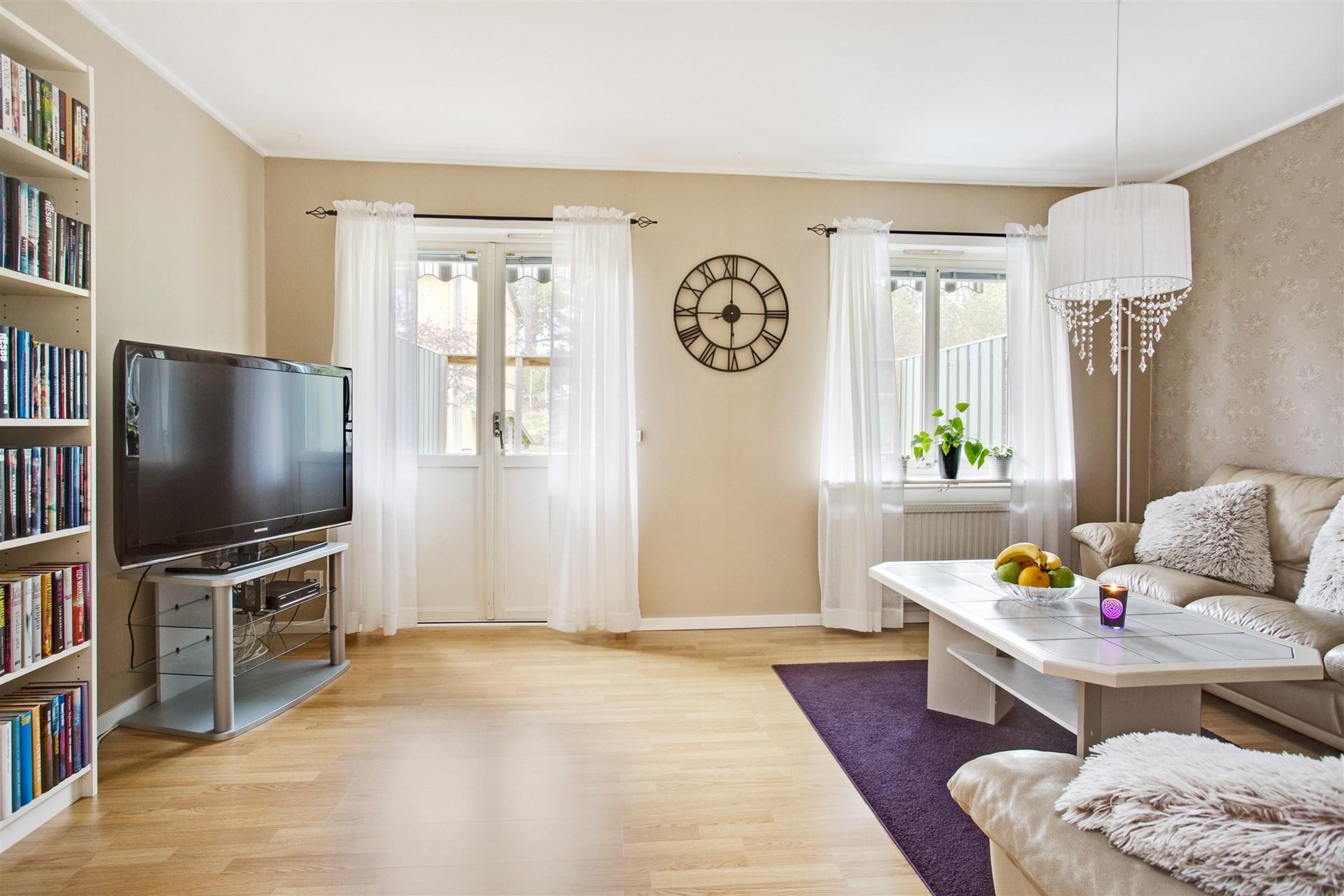 Ljust vardagsrum med fönster och utgång till altanen.