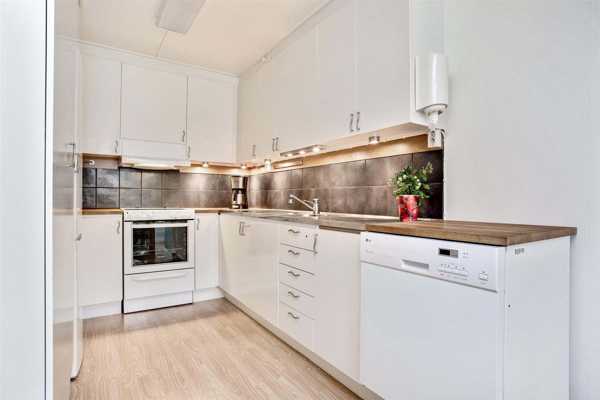 Fräscht kök med vita köksluckor och kakel över diskbänk.