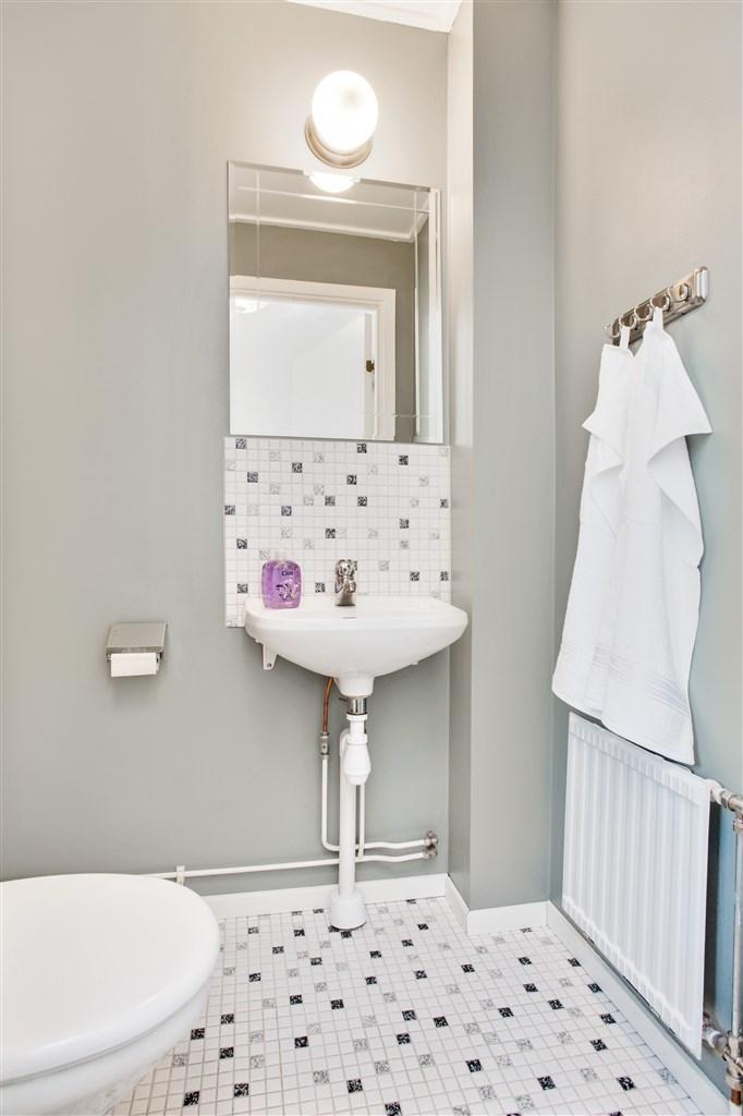 Wc med handfat, liten spegel och ett förvaringsskåp.