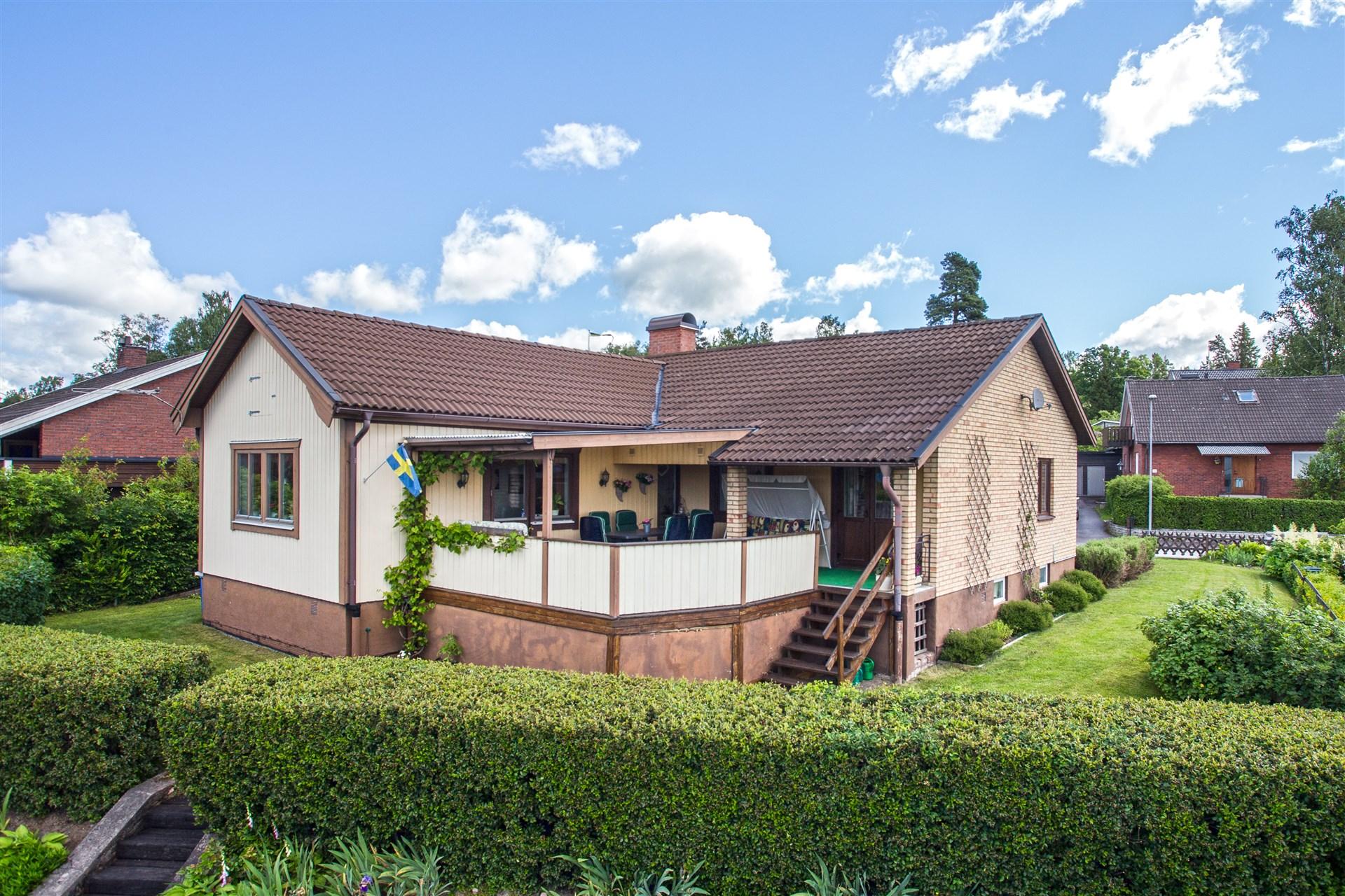 Villa med högt soligt läge och uppväxt trädgård. Baksidan med altan, delvis under tak.