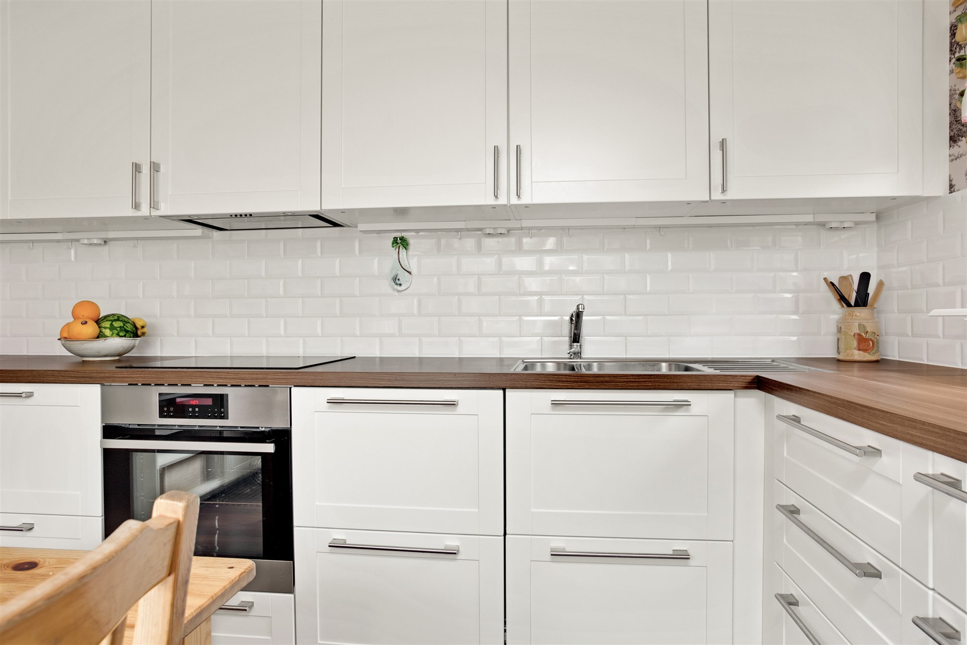Laninatklädda bänkskivor och både utdragslådor och överskåp i köket.
