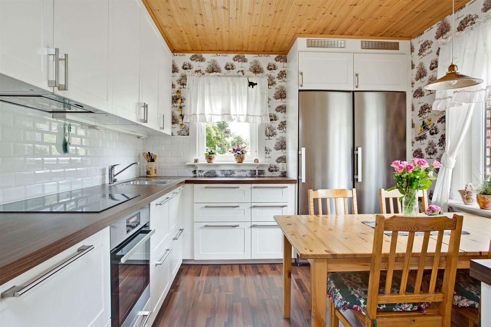 Fräscht och helrenoverat kök med vita köksluckor och vitt kakel över arbetsbänk.