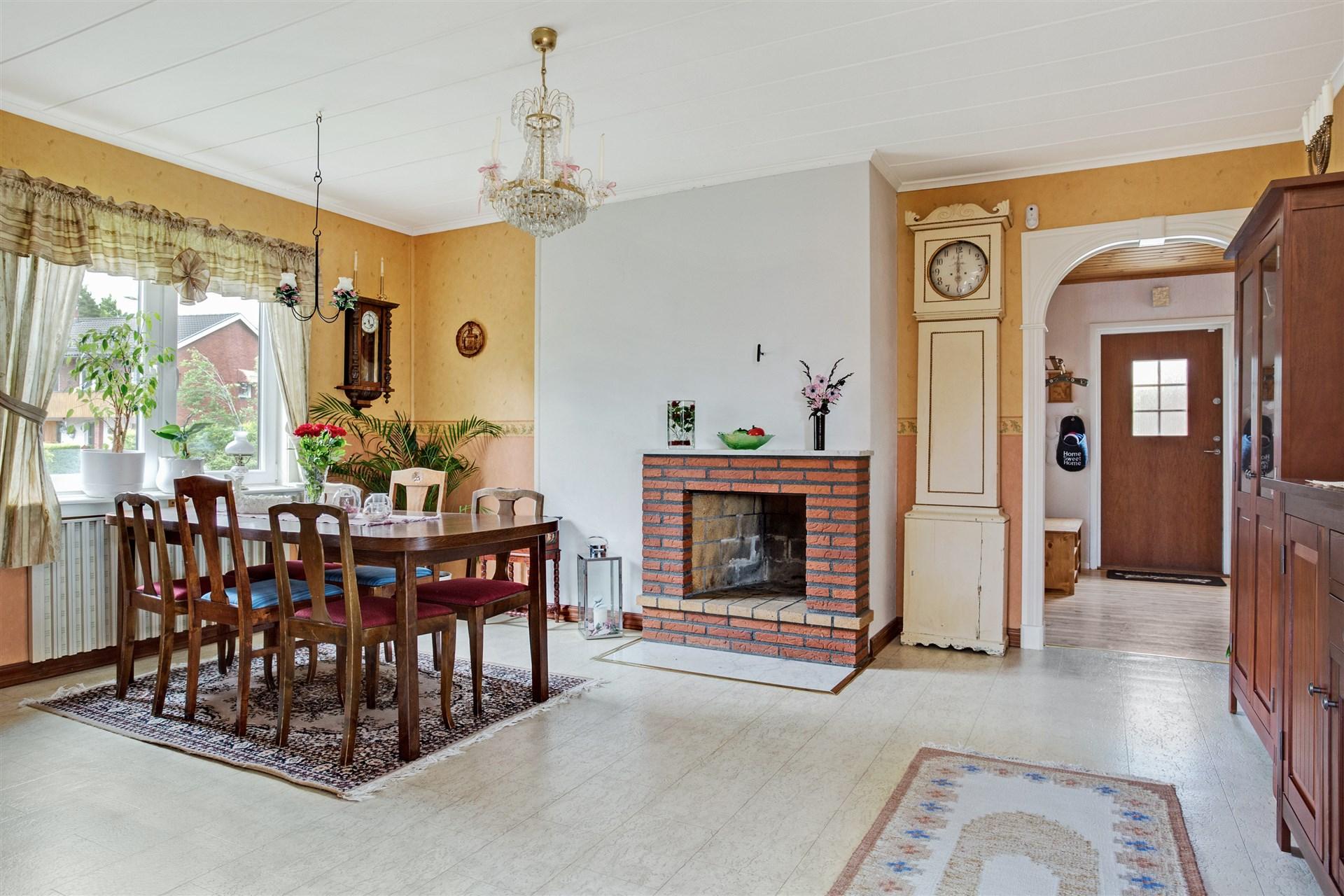 Vardagsrum med öppen spis och portal mot hallen.