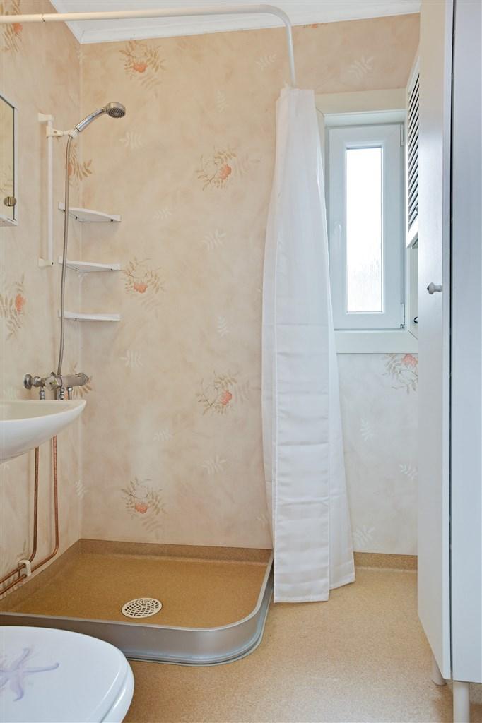 Dusch/wc med plastmatta på golv och vägg och 3 badrumsskåp.
