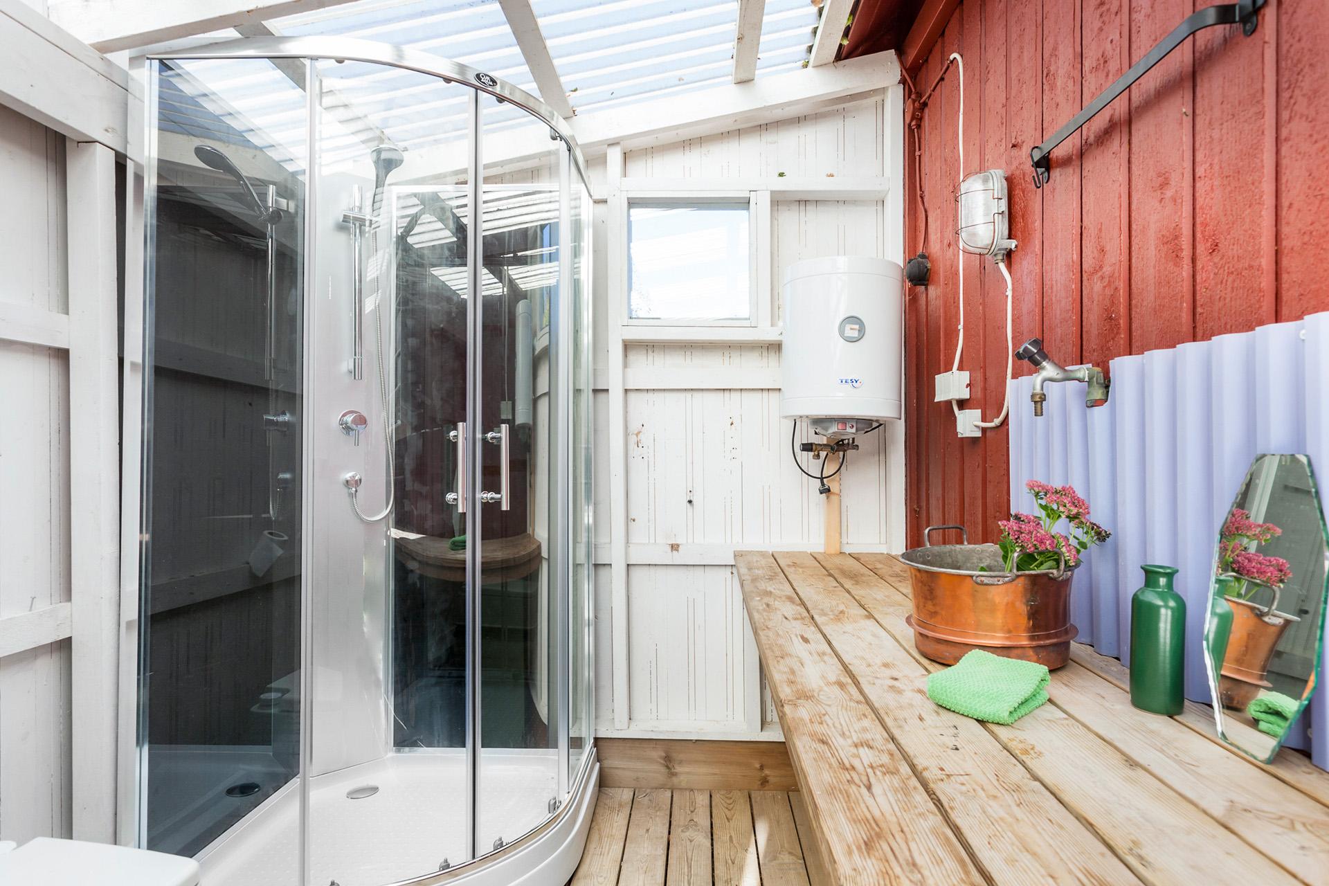 Duschkabin placerad i husets vidbyggda del med ingång från trädgården.