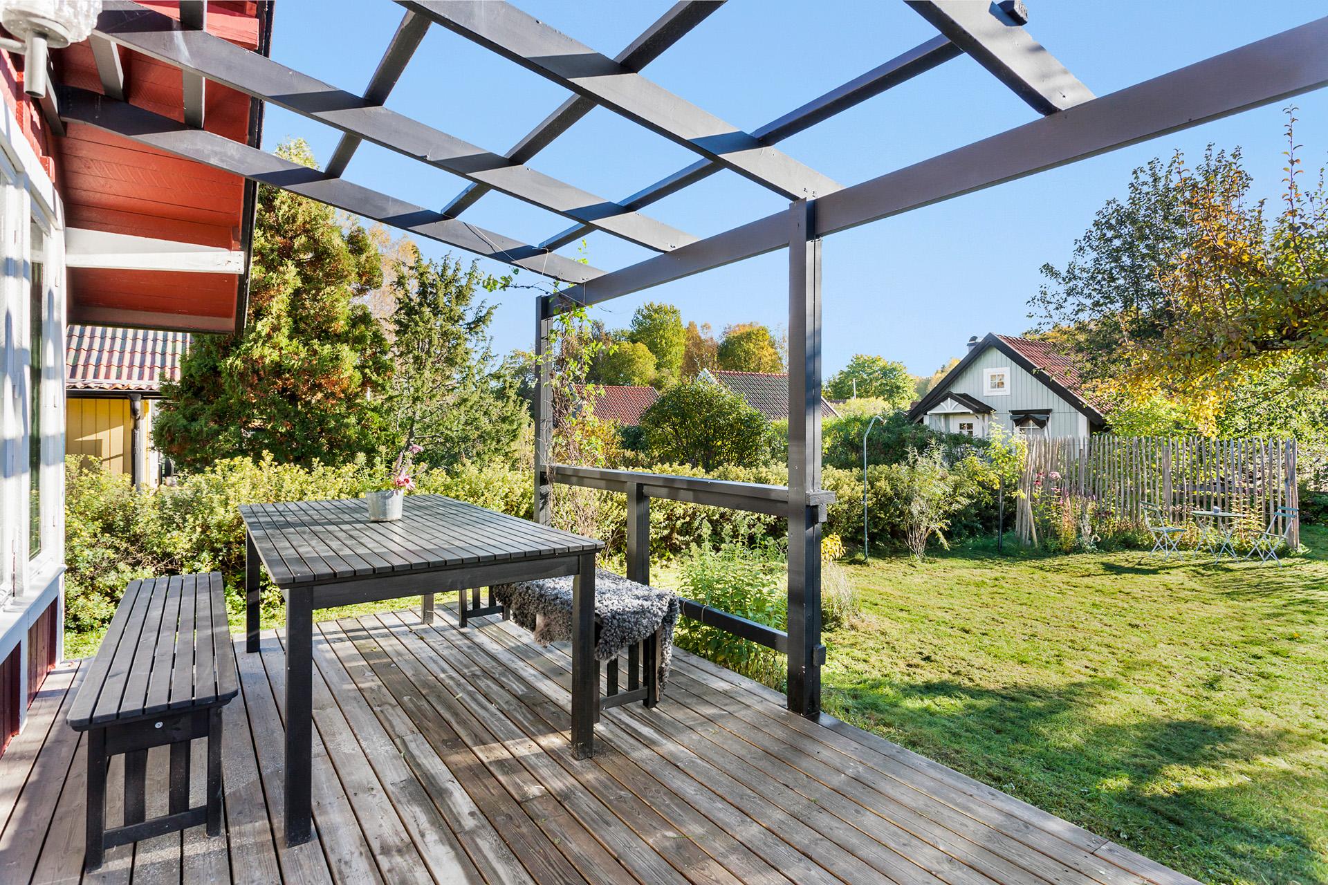 Från terrassen kan du blicka ut mot den fina trädgårdstomten.