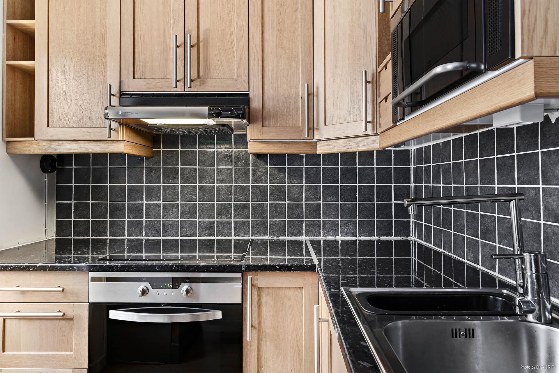 Kök med spishäll, spisfläkt, varmluftsugn, mikrovågsugn samt kombinerad kyl/frys