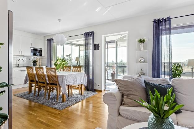 Öppen planlösning mellan kök och vardagsrum och utgång till den inglasade balkongen