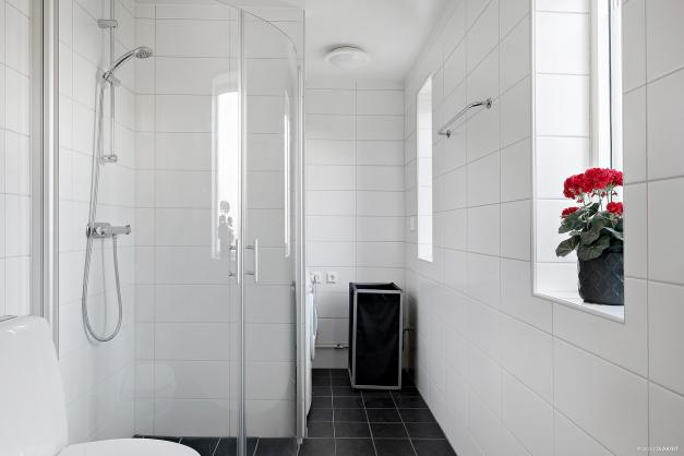 Helkaklat badrum med tvättpelare bakom duschen
