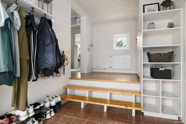 Välkommen in! Plats för ytterkläder i hall med klinergolv och ett par trappsteg upp till inre, delvis möblerbar hall som leder vidare in i huset.