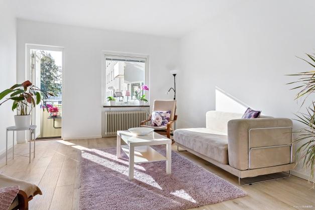 Ljust och fräscht vardagsrum med utgång till balkong