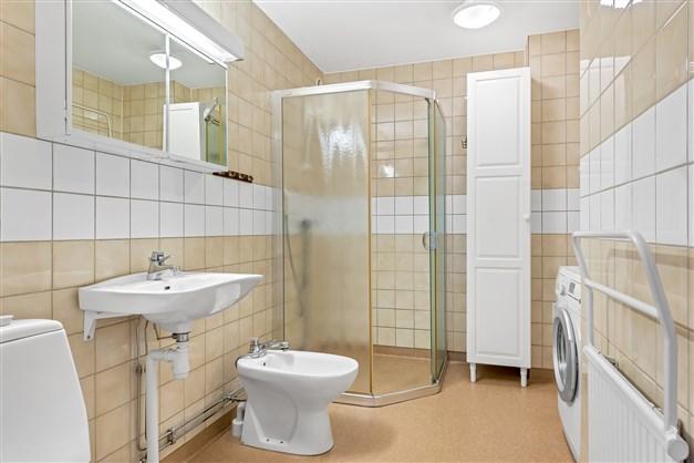 Badrum med dusch och tvättmaskin