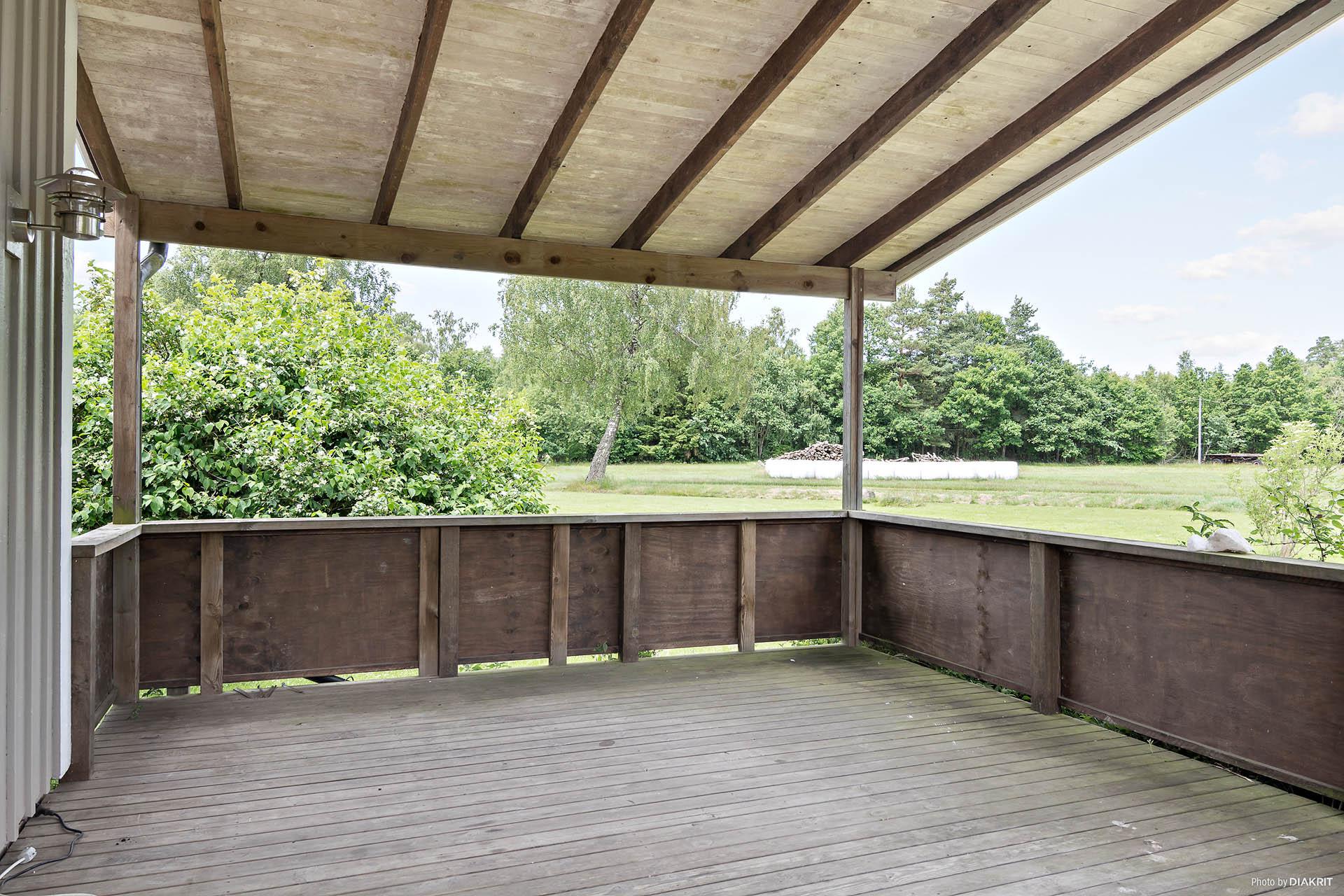 Stor veranda med tak, vyer över den stora tomten.