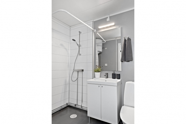 Badrum med wc, dusch och plats för tvättmaskin.