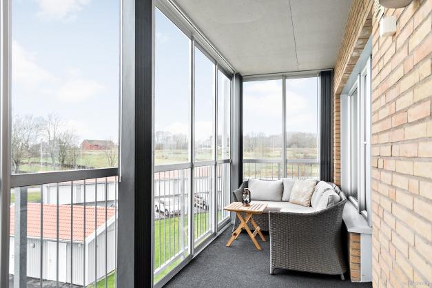 Från vardagsrummet når du den inglasade balkongen som lätt blir ett favoritrum stora delar av året