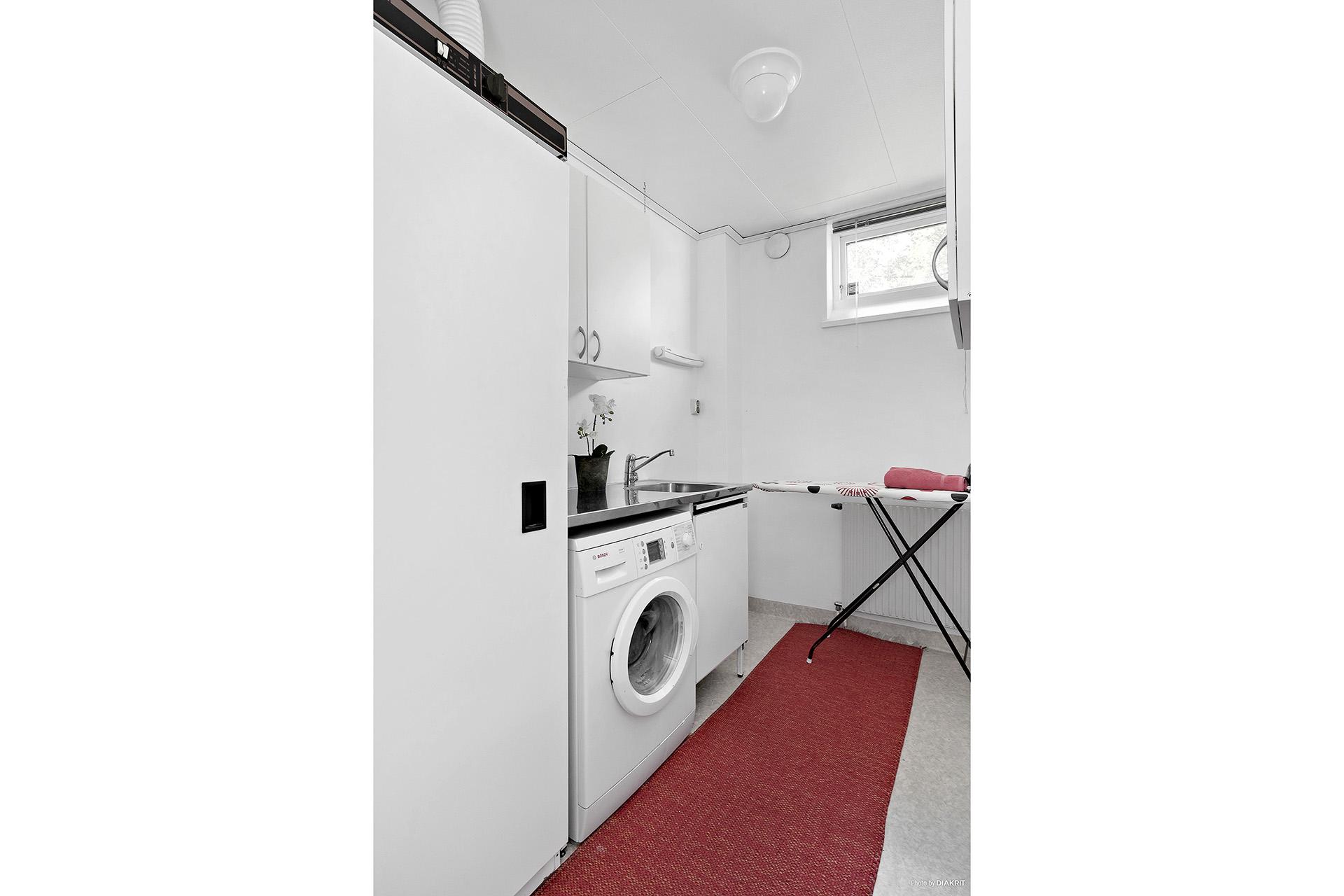 Rymligt tvättstuga med tvättmaskin, torkskåp, allbänk samt väggskåp.