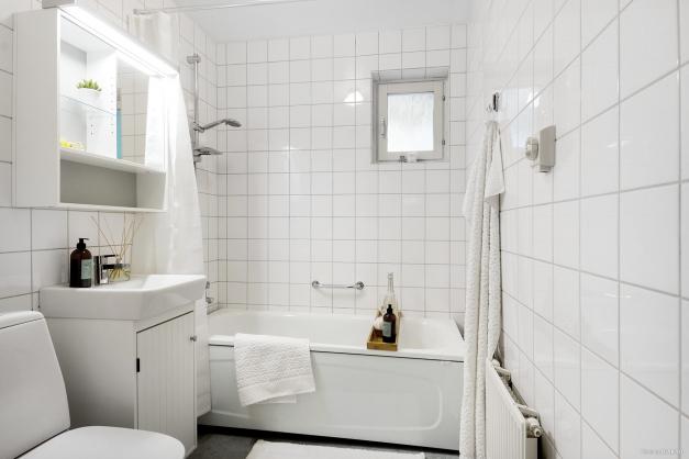 Badrum med kaklade väggar och våtrumsmatta.