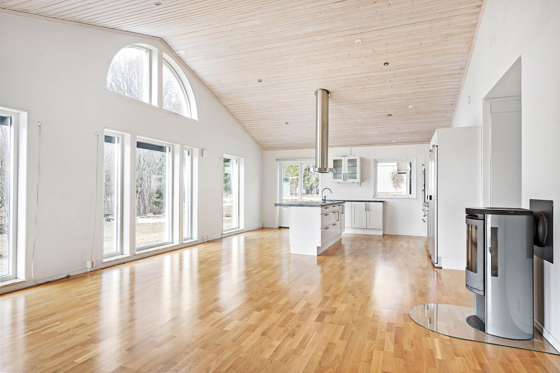 Ljust och luftigt vardagsrum med öppen planlösning mot köket.