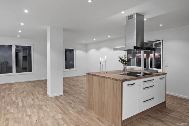 Kök med öppen planlösning mot det luftiga vardagsrummet.