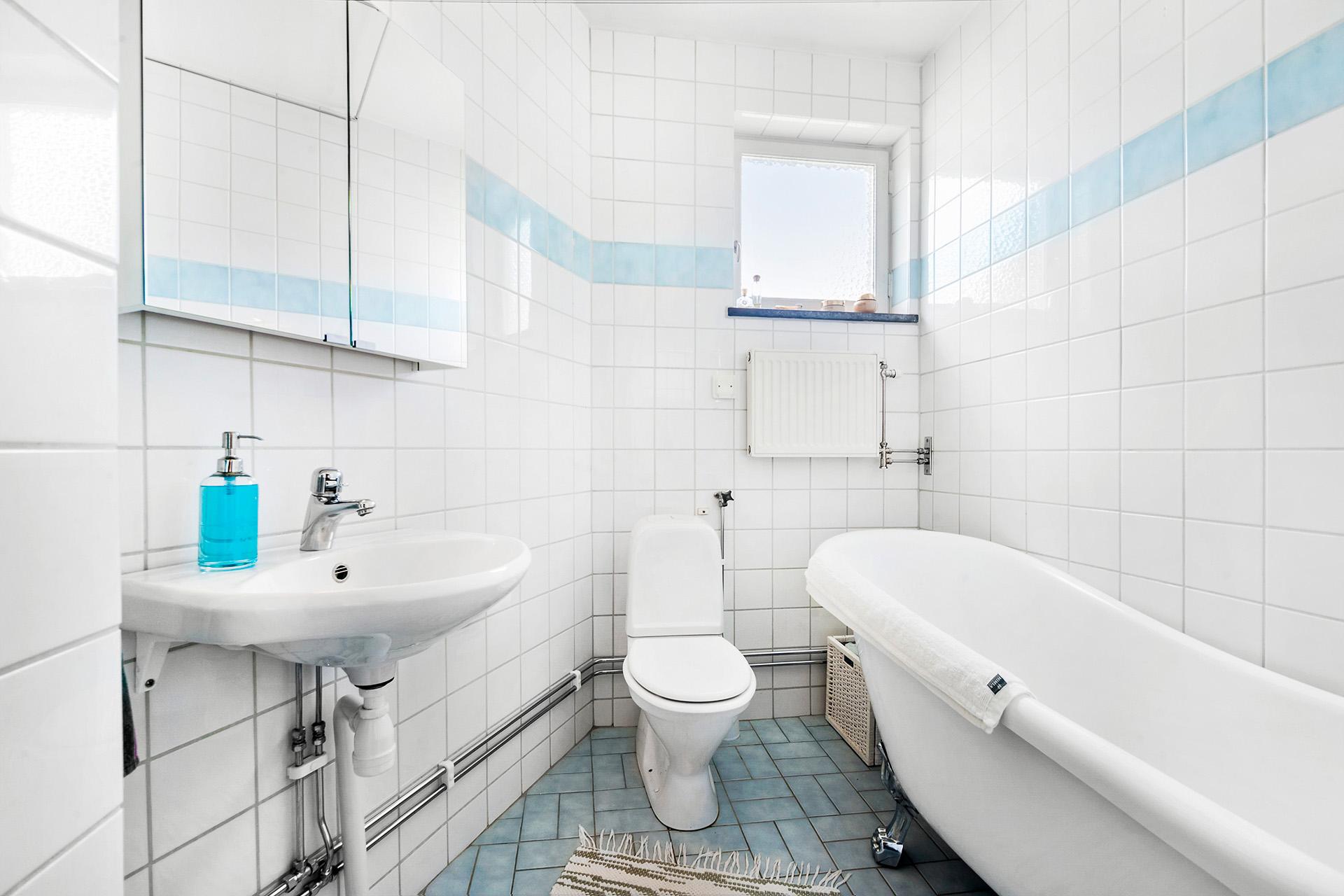 Helkaklat badrum med fönster.