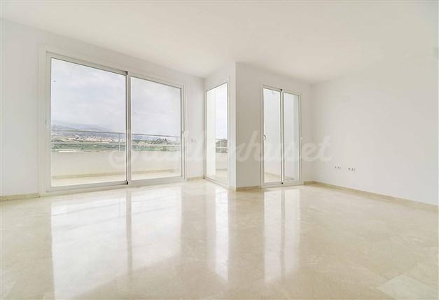 Ljust vardagsrum, marmorgolv och stora glasdörrar till balkongen