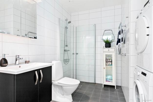 Helkaklat badrum med tvättmaskin och tumlare