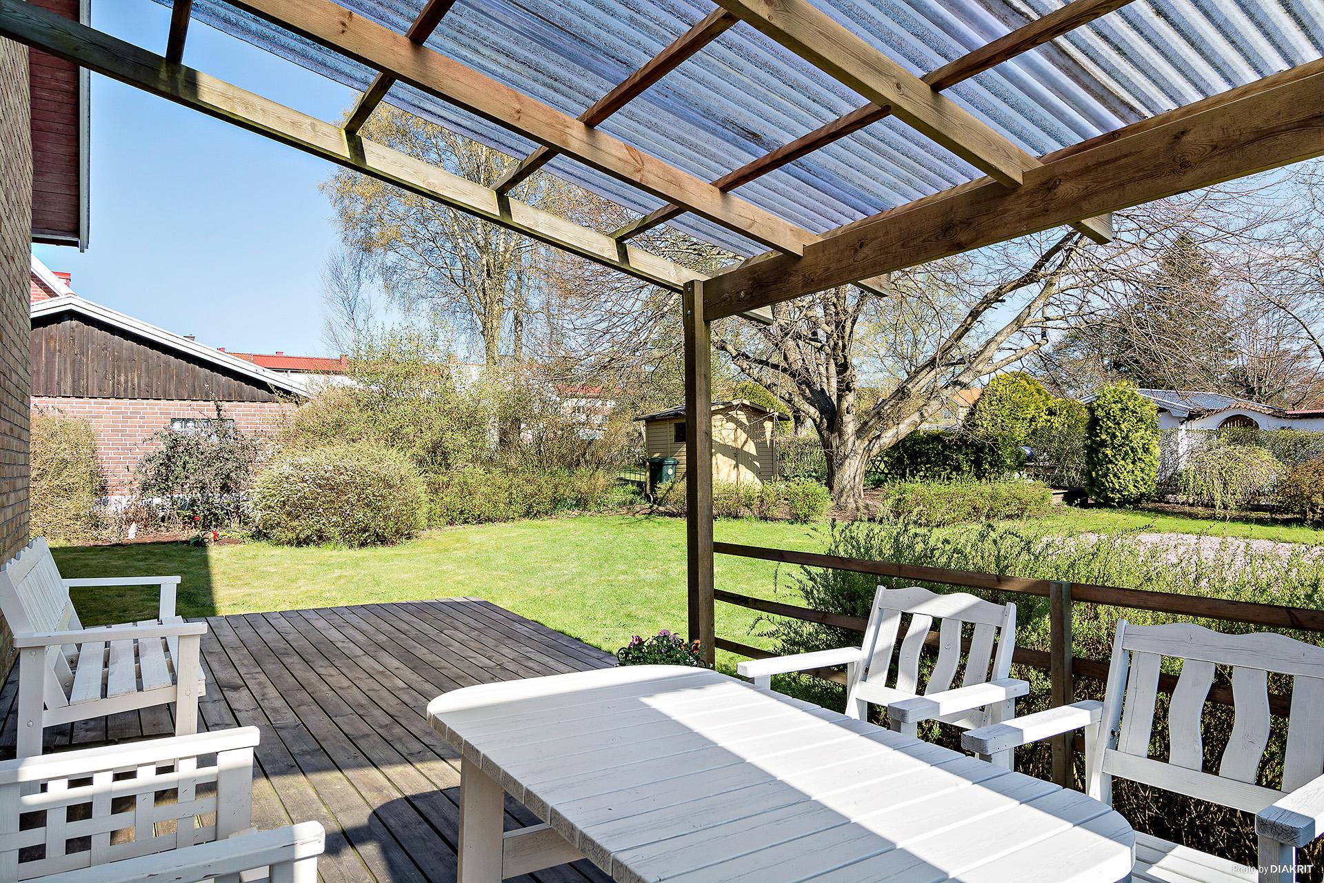 Överbyggd altan på gavel mot trädgården.