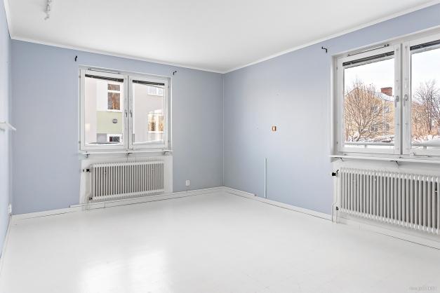 Ljust vardagsrum med två fönster