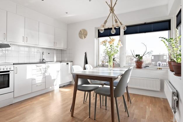 Ljust och rymligt kök utrustat med spis, fläkt, kombinerad kyl/frys samt diskmaskin. Vy över innergården.