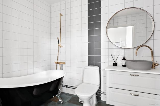 Helkaklat badrum utrustat med badkar, wc, handfat med kommod samt kombinerad tvättmaskin & torktumlare.